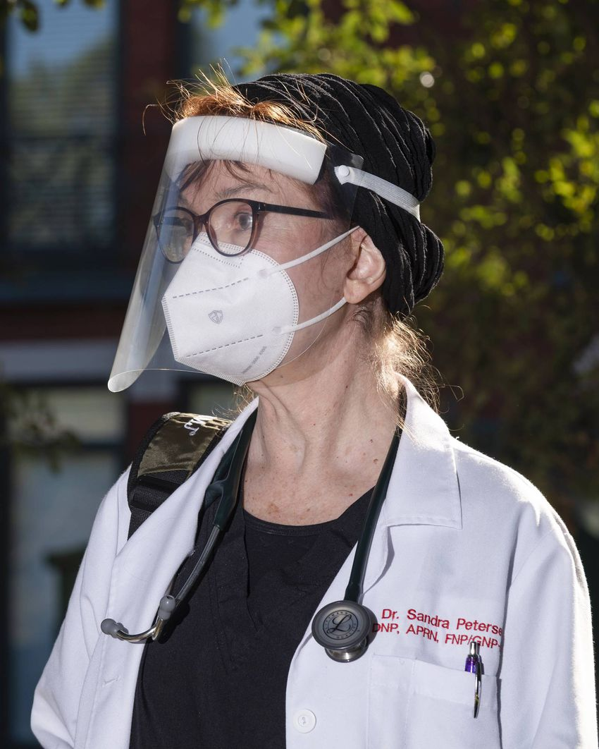 Medical doctor Sandra Petersen wearing some of her personal protective equipment before seeing COVID-19 patients inside The …