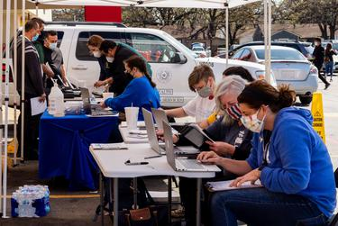 Volunteers and officials with the Dallas County Department of Health and Human Services register people for the COVID-19 vaccine at an event in Irving on March 19, 2021.