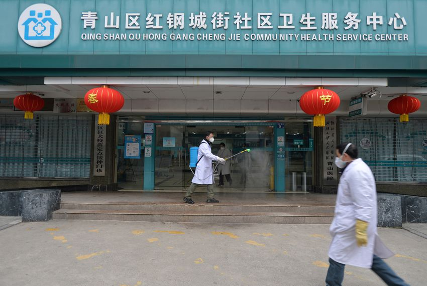 A doctor disinfects the entrance of a community health service center, which has an isolated section to receive patients with mild symptoms caused by the novel coronavirus and suspected patients of the virus, in the Qingshan district of Wuhan, Hubei province, China, on Feb. 2, 2020.