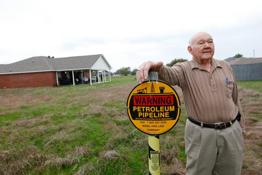 Jim Howell stands on the easement of the Exxon Mobile Pegasus pipeline which runs through his property in Gun Barrel City ...