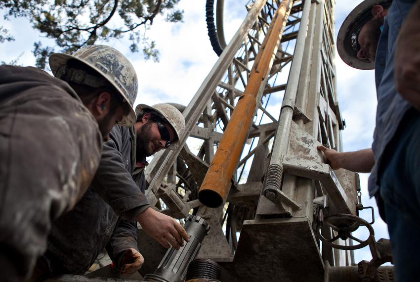 Workers with Bee Cave Drilling install a jackhammer bit on the drilling rig while putting in a water well on a private lot i…