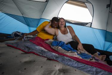 Gilbert Jones, left, and Crystal Brimm, right, share an intimate moment in their tent on Oct. 24, 2019 located under the TX-71 and W. Ben White Blvd. overpass.