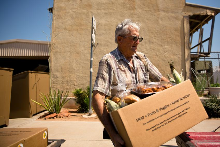 A volunteer loads a box of groceries into a truck for delivery to a nearby community in the the panhandle.