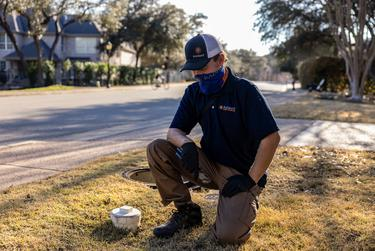 Zachary Shockency, a technician with Radiant Plumbing, turns off a City of Austin water valve at a home in West Austin on Feb. 24, 2021.