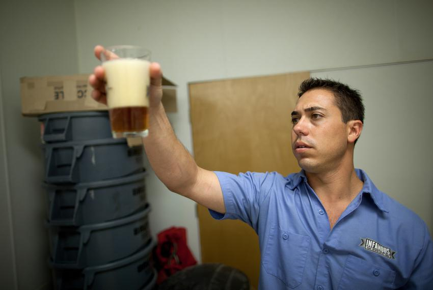 Matt Bitsche, chief engineer and head brewer at Infamous Brewing Company, inspects a pint of beer for clarity, aroma and ove…