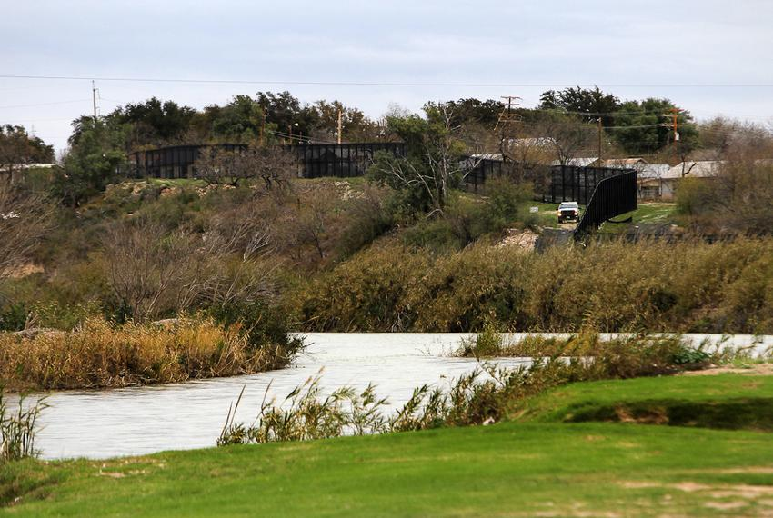 The Rio Grande and a towering border fence separate Eagle Pass, Texas from Piedras Negras, Mexico, Saturday, February 4, 2...