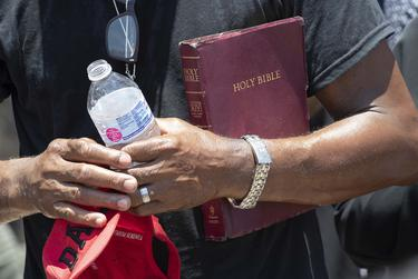 A Dallas minister holds a Bible outside the immigrant detention center in McAllen.