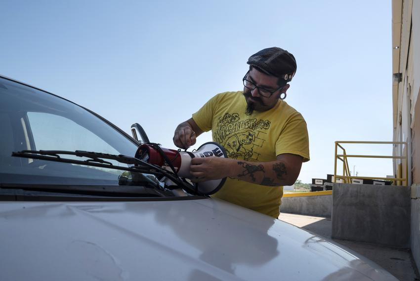 Marco Lopez, who works with La Union Del Pueblo Entero, L.U.P.E., installs a megaphone on to his vehicle to drive around c...