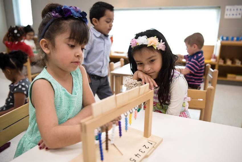 Cattleya Covarrubias (left) helps Aryana Huerta with a lesson at East Texas Montessori Prep Academy.