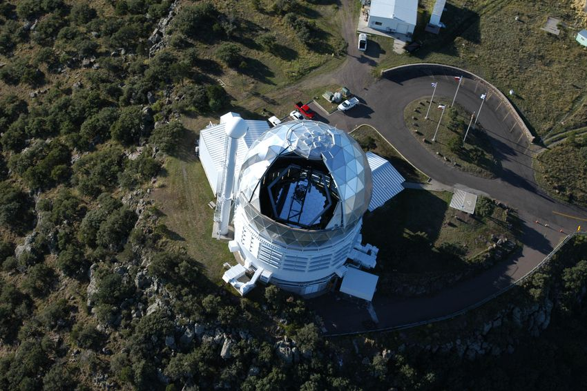 Blue sky reflects in the primary mirror of the Hobby-Eberly Telescope at McDonald Observatory in this aerial view. The mirror is made of 91 individual segments. A dark instrument platform, which sits at the top of the telescope, partially obscures the mirror.