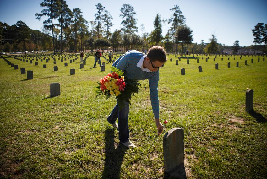 Anthony Ormsbee places flowers with other volunteers at the Texas Department of Criminal Justice's Captain Joe Byrd Cemetery…