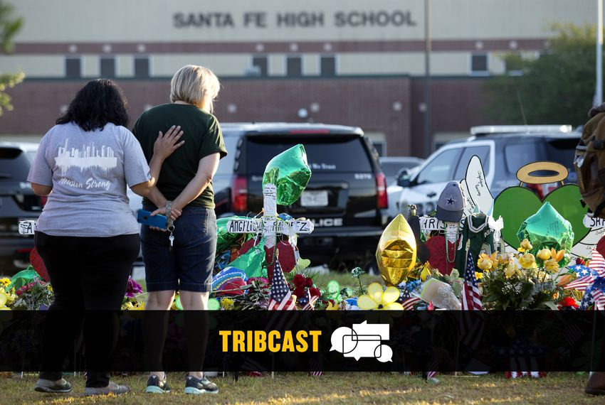 People stand before a makeshift memorial in front of Santa Fe High School.