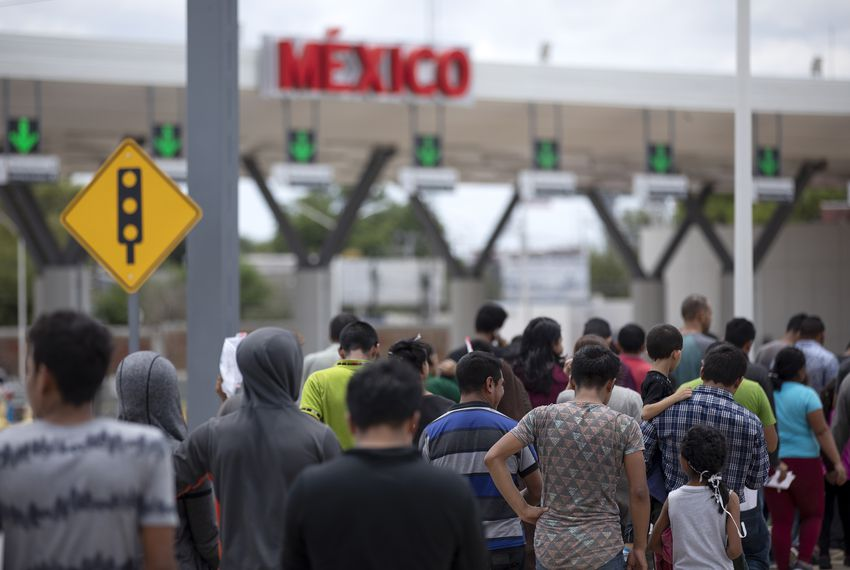 Migrants walk across International Bridge Two into Nuevo Laredo from Laredo. They requested asylum in the United States but were returned to Mexico to await their court proceedings.