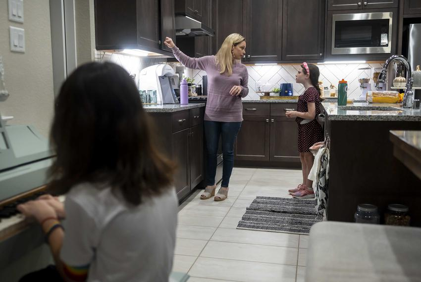 Danielle Miller prepares her two children for school in their home in Magnolia on Oct. 21, 2021.