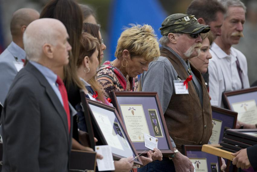 Family members of those killed in 2009 during the Fort Hood shooting receive their awards at a ceremony on April 10, 2015. A…