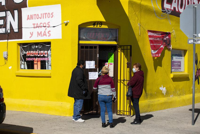 People wait outside to pick up their food order on day one of the shelter-in-place order that was put in place by the county…