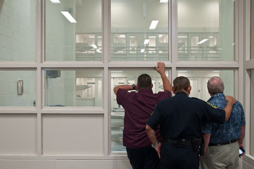 Jail officials watch as the ventilation system clears a day room of fumes released by a smoke bomb.
