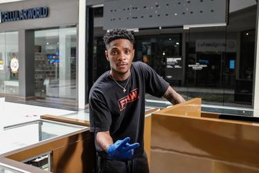 Yanick Almeida, 23, works at one of the jewelry kiosks at the Barton Creek Square Mall in Austin. The mall recently opened for limited business.