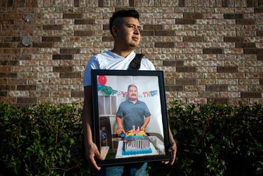 Cristobal Onofre holds a photo of his father, Benito, who died in July from COVID-19. The virus has disproportionately affected Hispanic families in Houston.