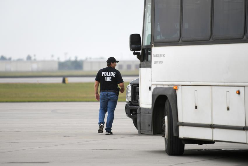 A law enforcement official walks past a transport bus used to carry migrants in U.S. Immigration and Customs Enforcement (IC…