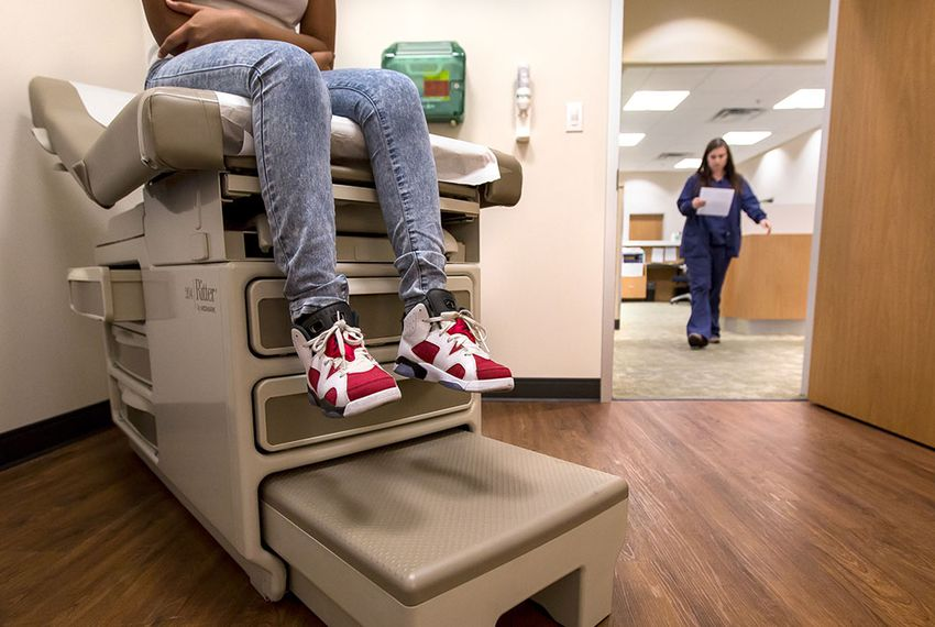 Eighth-grader Montanique DeShay waits as Ashlyn Brooks, medical assistant at MedSpring Urgent Care in Austin, comes to check on her on Wednesday.