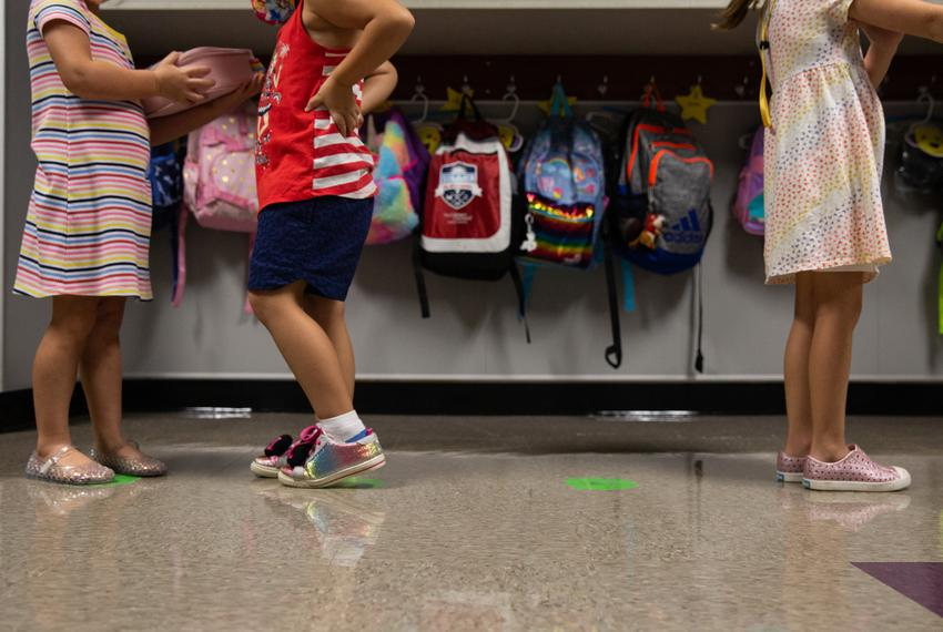 Kindergarten students line up on social distancing markers on the first day of in-person classes at Highland Village Element…