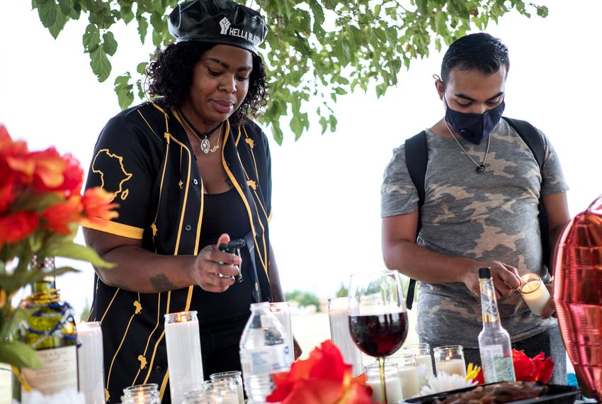 From left, Lisa LaFlor and Isaiah Vale, light candles during a vigil honoring the victims of the Walmart shooting.