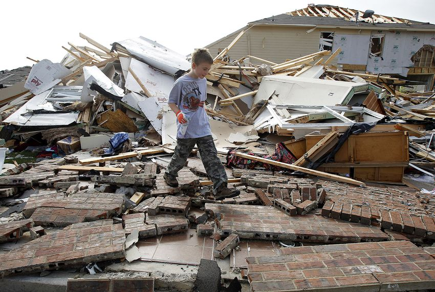 Duncan Winters, 10, walks through the remains of his grandmother's home during the cleanup effort in Forney on April 4, 2012. Thousands of residents were without power and hundreds of flights canceled as authorities surveyed the damage a day after up to a dozen tornadoes struck the densely populated Dallas-Fort Worth area.