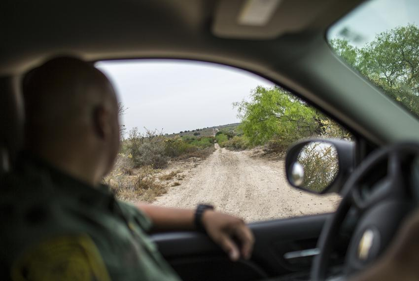 Border Patrol Agent José Perales examines tracks on an unpaved gravel road while looking for unaccompanied child migrants an…