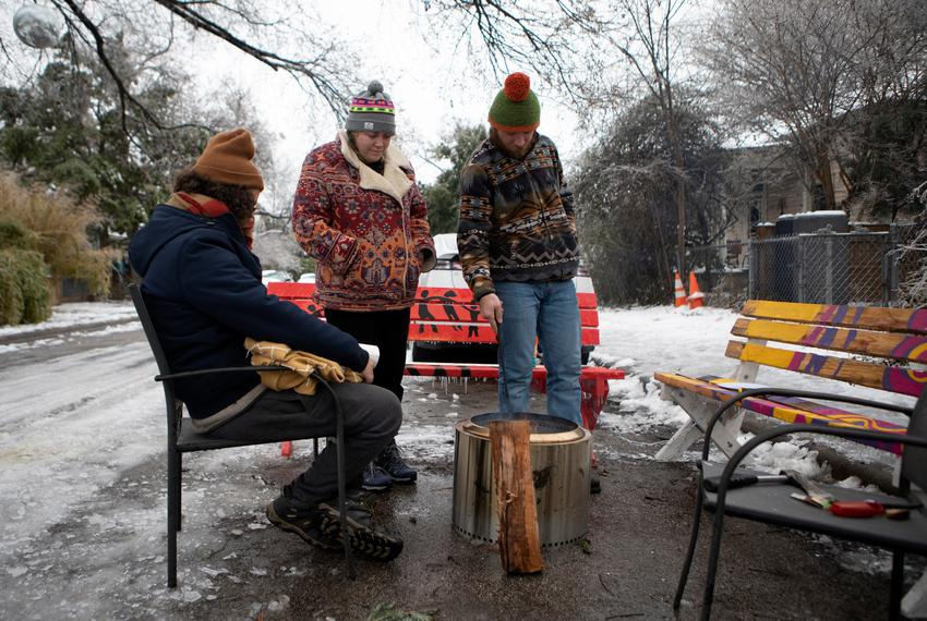 From left to right, Martin Xoxa, Chelsea Pursley and Joe Williams build a fire to keep warm outside of Pursley's home in Eas…
