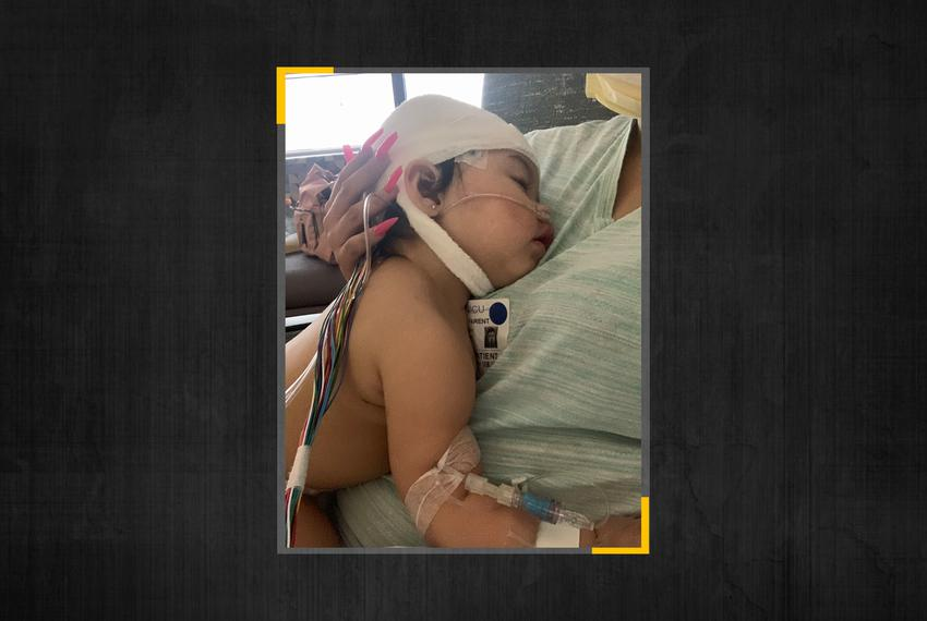 Ava Rivera, 11 months old, lies on her mother's chest after being treated for COVID-19.