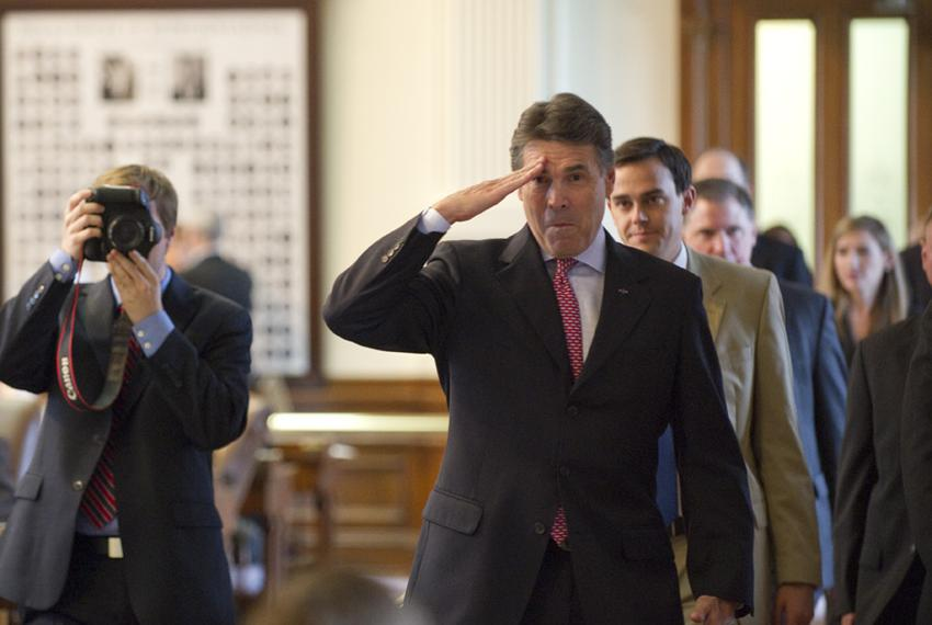 Gov. Rick Perry makes a playful salute to the son of State Rep. Craig Eiland, D-Galveston, as he walked through the House ch…