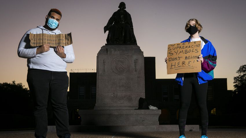 Shifa Rahman, left, and fellow protestor Blaise hold protest signs at the base of the William Marsh Rice statue on the campu…