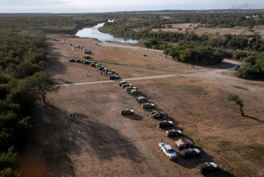 Military and Texas Department of Public Safety vehicles create a cordon around migrants sheltering in a nearby makeshift bor…