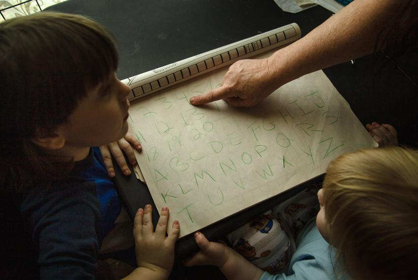 Lucille Hammash goes through the alphabet with two of her grandchildren, Noah and Kenny Proctor in their house in central Ho…