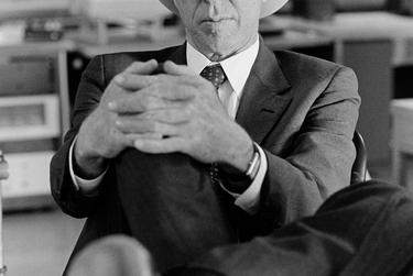 """Portrait of Temple Dickson, 1988.  For Newton, this image of former state Senator Temple Dickson is an example of what he strived to capture for every politician he photographed.  """"I tried to find a shot that was rough hewn with lots of character that didn't look conventional,"""" he said. """"Of necessity political stuff is usually heroic, and so what I try to do is avoid the outright heroic, this is more of a character study.""""  Newton took the photograph as they were transitioning between set-ups during a portrait session for the Dickson's initial bid for Texas Senate in 1988 after finding him resting with his legs up on the desk.    """"It was absolutely genuine; he wasn't posing,"""" he said. """"It was him.""""  The Sweetwater Democrat was a trial lawyer who had served in the state House, where he wrote a 1969 law holding local and state governments legally accountable for negligent acts."""