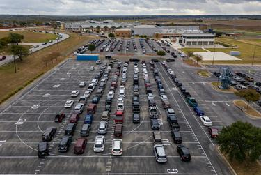 Hundreds of cars line up in the parking lot of Lehman High School in Kyle to receive food from the Central Texas Food Bank.