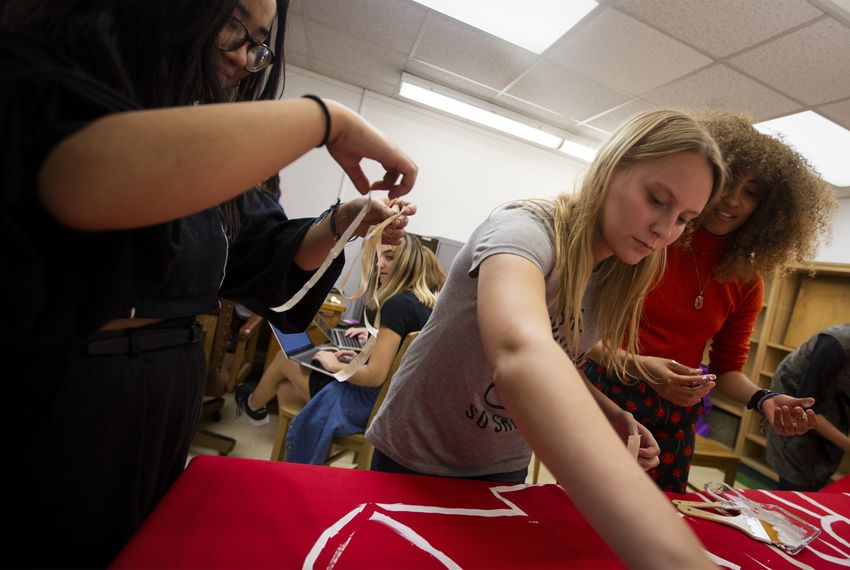 From left: Lynn Huynh, Shelby Hobohm and Simone Harry paint a banner for an upcoming protest during a meeting of the Coalition Against Sexual Misconduct.