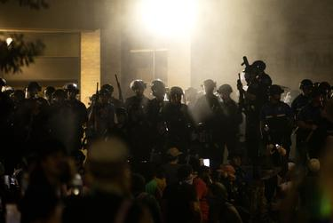 Austin police officers look towards protesters after firing tear gas at the crowd. May 30, 2020.