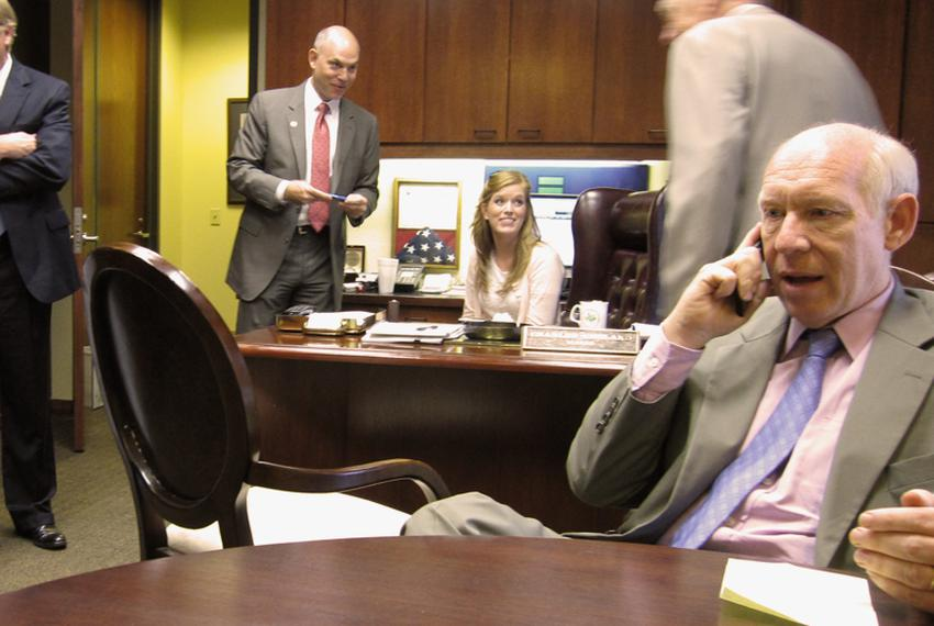 Bill White, on the phone in Grand Prairie Mayor Charles England's office. Behind him, from left to right, are Rep. Kirk Engl…