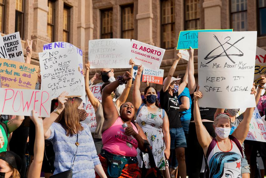 Pro-choice attendees chant and stand to block a small pro-life counterprotest from view during the Womenís March ATX at the …