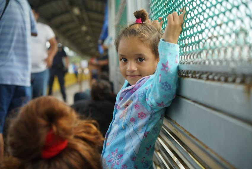 Genesis, a 5-year-old girl from Honduras traveling with her mother and brother, waits on the international bridge between Br…