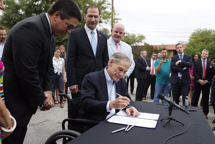 As lawmakers and Lyft and Uber drivers look on, Gov. Abbott signs House Bill 100, which creates statewide regulations for ri…