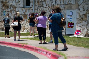 People wait in 100 degree weatheto vote at the Pflugerville ISD Rock Gym on July 14, 2020.