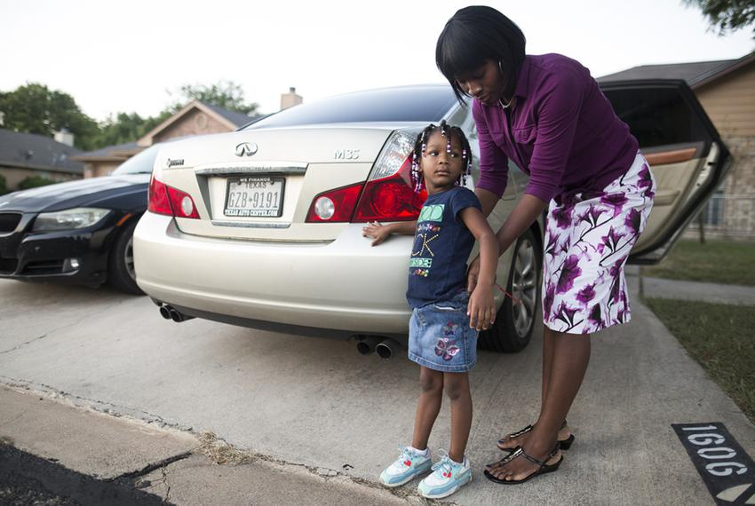 Brittany Phillips tucks in her daughter Leah's shirt before taking her to school.