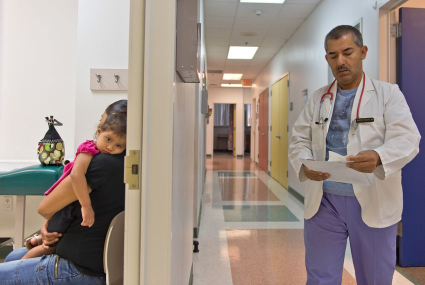 Yesenia Alvarado holds her daughter, Medicaid patient Melanie Almaraz, 2, while waiting to see Dr. Alberto Vasquez for the treatment of a fever at the Su Clinica Familiar in Harlingen on Jul. 9, 2013.