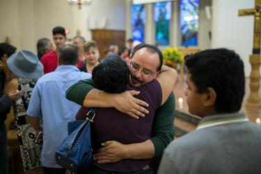 A man and woman embrace as Nadra Alvarez and her mother Angelina Alvarez pray after a candlelight vigil at a Catholic church, Saturday, August 3, 2019, in El Paso, Texas. Photo by Ivan Pierre Aguirre