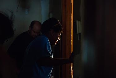 Charla Gilliam, a specialist at Adult Protective Services, peers through a doorway at an elderly woman she's visiting in June as the woman's son listens to their conversation. Gilliam was assigned to the case because the woman was neglecting herself.