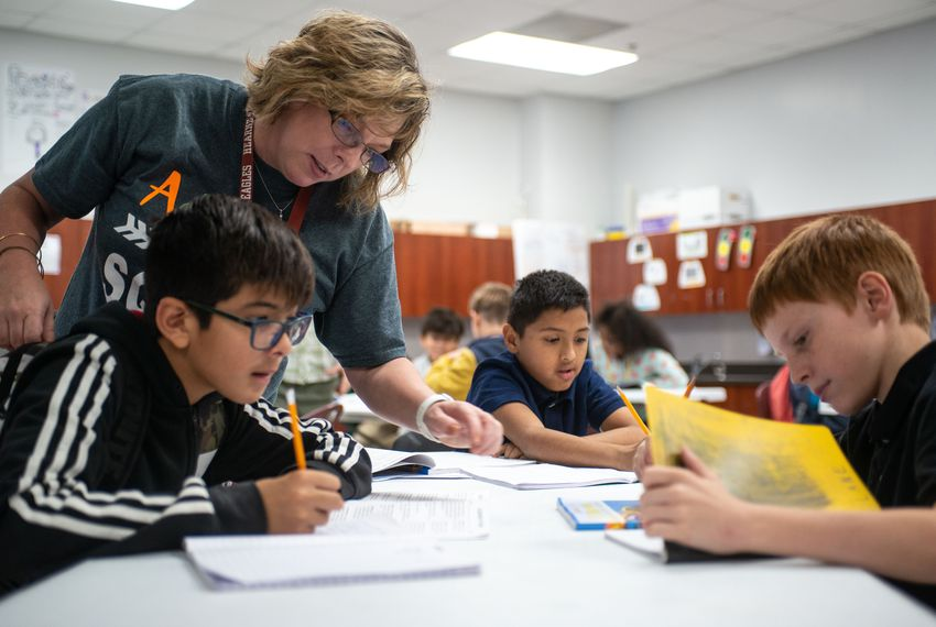 Hearne Elementary School Principal Stephanie Heinchon assists sixth grade students Gabriel Ramirez (left), Jesus Munoz and Lane Endsley with science classwork.