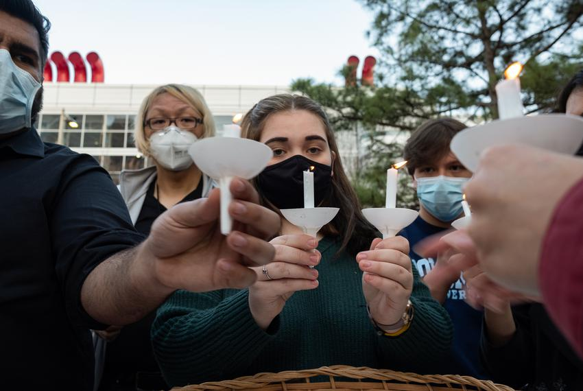 Volunteers light candles at Discovery Green on March 20, 2021, in Houston. People gathered for the Stop Asian Hate Vigil and…